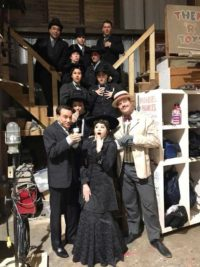 full cast in funeral costumes backstage